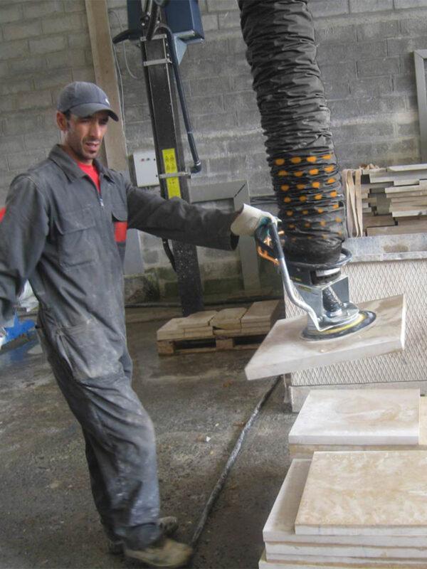 man lifting paper sacks using handheld vacuum lifter