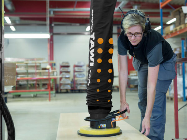 Woman lifting and moving sheet with vacuum lifter