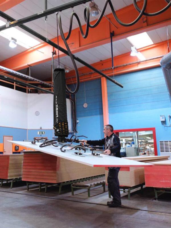 Man lifting large sheets of wood using handheld vacuum lifter