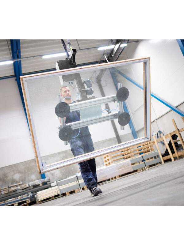 Man gripping and lifting big metal sheet using a handhold vacuum lifter system