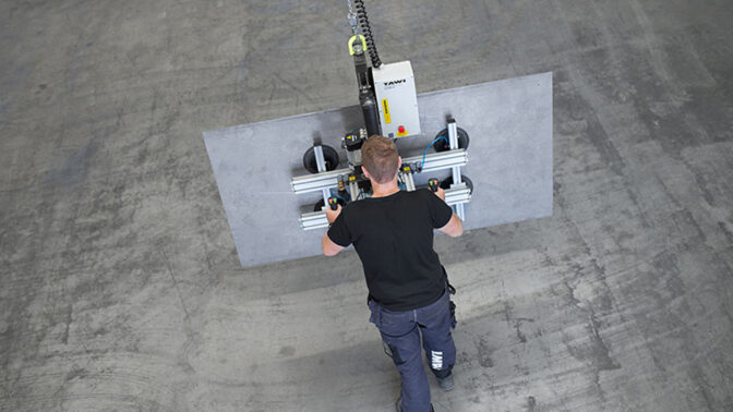 Man lifting sheet with vacuum yoke sheet gripper