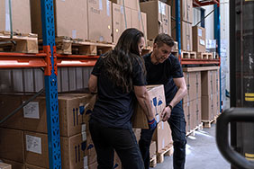 Two people lifting heavy box in warehouse