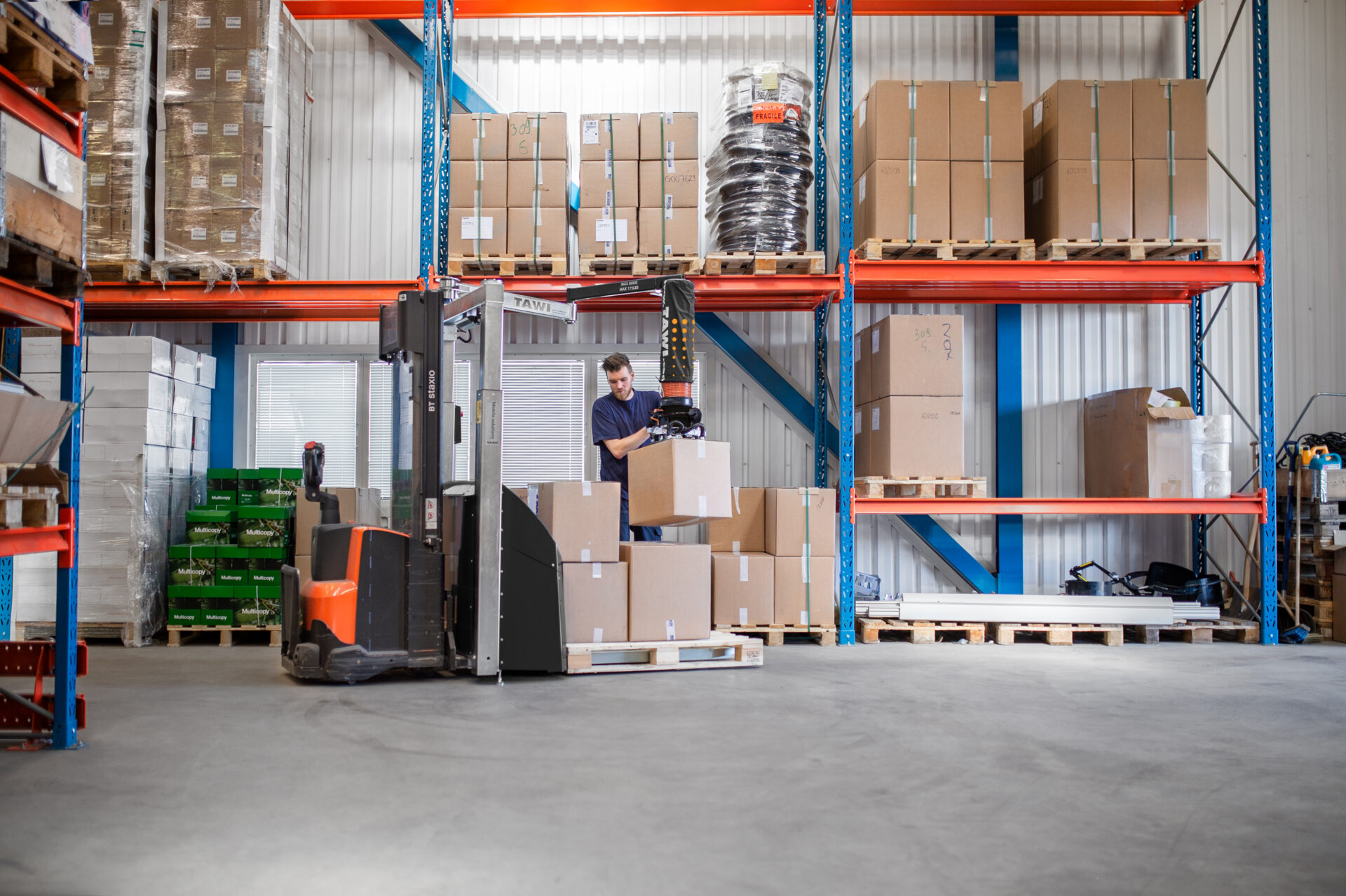 Man lifting and packing heavy boxes using a vacuum lifter trolley in stock