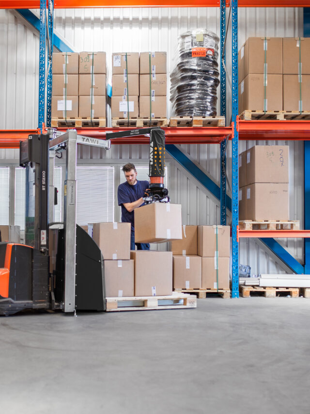 Man lifting and packing heavy boxes using a mobile vacuum lifter in stock