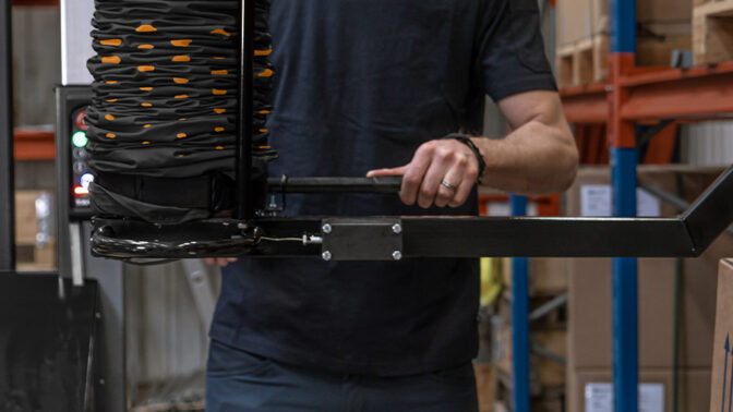 Mobile order picker with easy reach tool lifting boxes from pallet rack