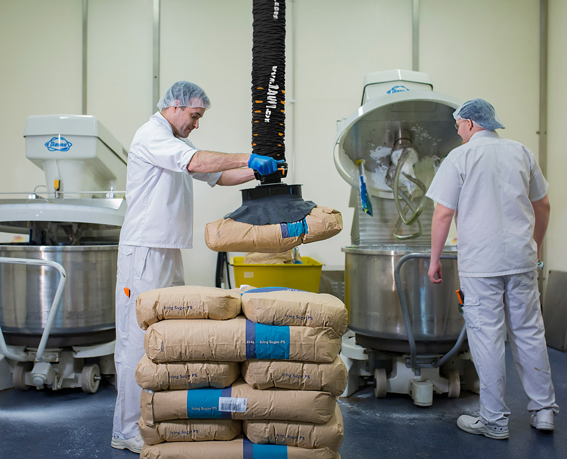man lifting and stocking paper sack with food using handhold vacuum lifter