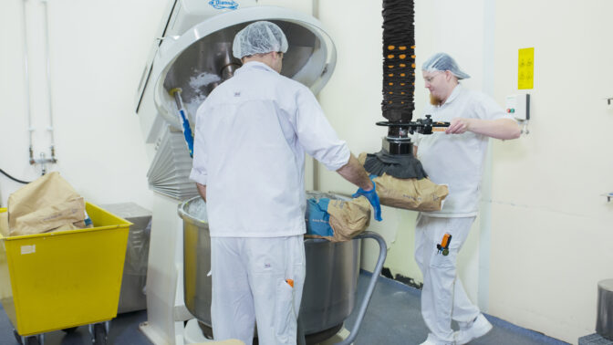 lifting sack of flour to empty in mixing vessel in bakery
