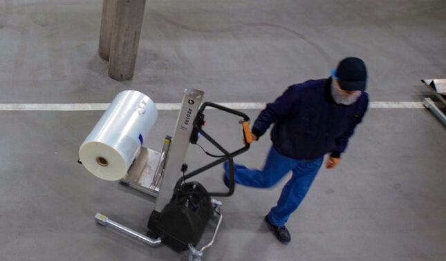 Man Lifting and moving plastic roll with lifting trolley