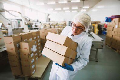 Woman manually lifting three boxes in sensitive environment