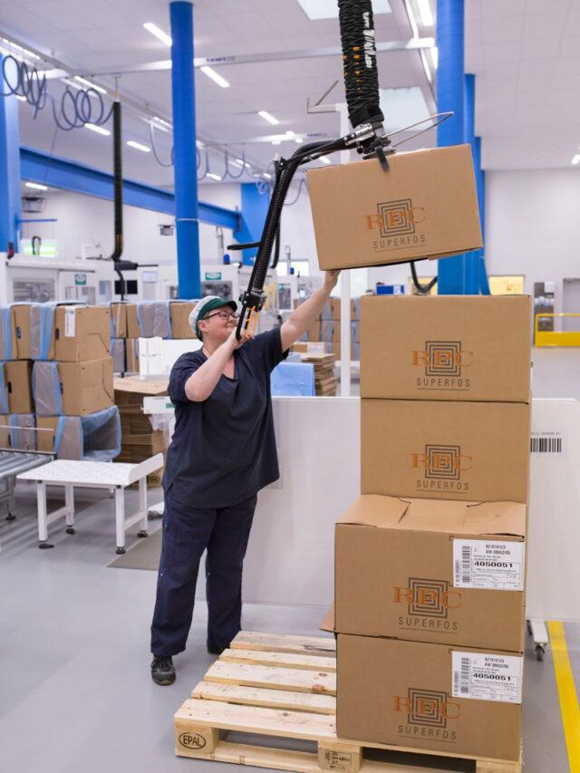 Woman lifting box above shoulder height using handheld vacuum lifter