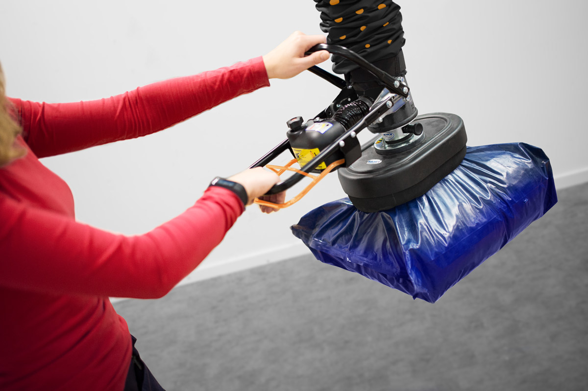 Lifting and moving plastic sack using handheld vacuum lifter