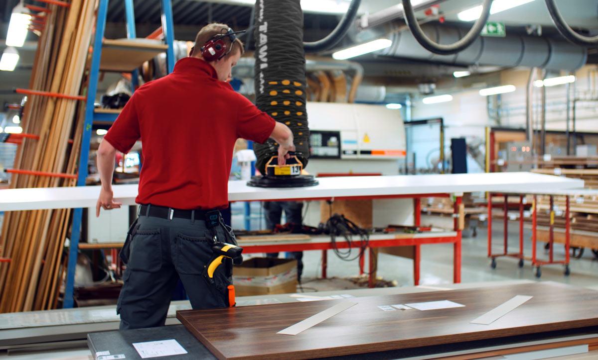 Man lifting large board with handheld vacuum, lifter
