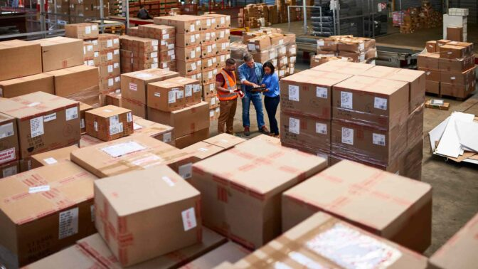 Warehouse workers standing together amongst palletized boxes