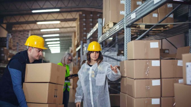 Warehouse workers carrying multiple boxes to pallet rack