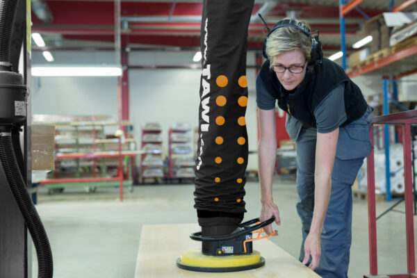 Woman lifting up sheet wood from the floor using a handhold vacuum lifter