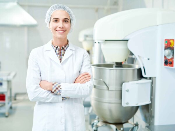 A smiling woman standing in a food industry environment