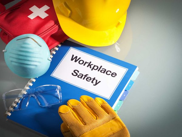 Workplace health & safety guide on a table with helmet, first aid kit, gloves and glasses